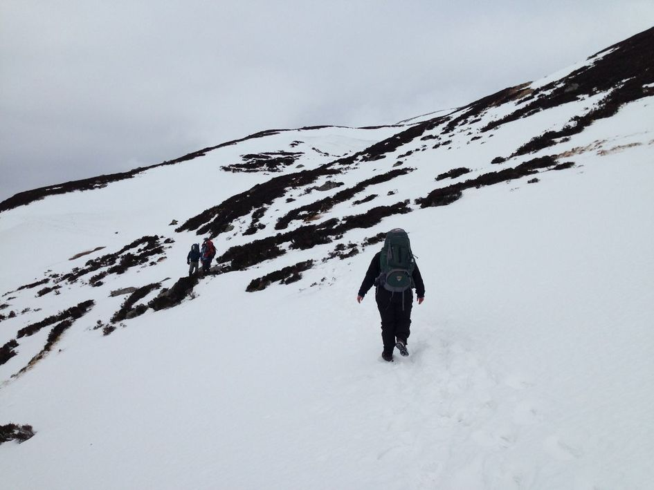 Walking through the thick snow on the mountain side.