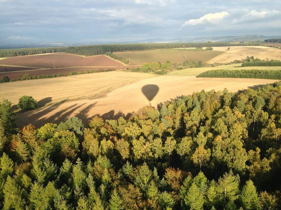 A beautiful shadow of the hot air balloon over the fields in the distance.